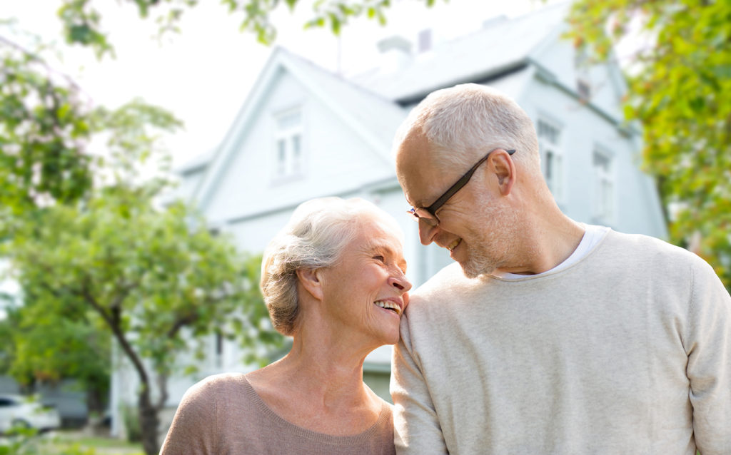 senior couple with reverse mortgage house in background