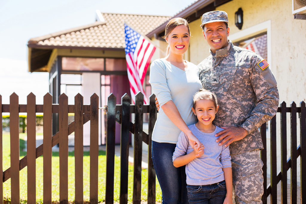 family in front of new house bought with va loan